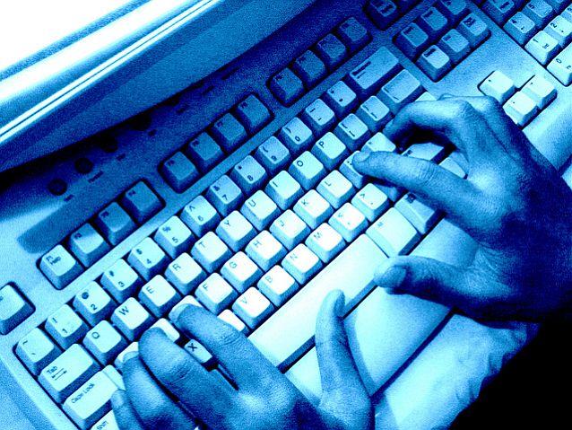 Ręce piszą na klawiaturze komputera